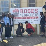 group in front of Roses in Concrete Community School