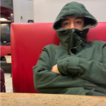 Chris sitting in chair with hoodie zipped up, half-covering his face