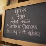 chalkboard sign in dining hall with fruit options