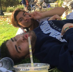 Friends lying on grass drinking from plastic cup