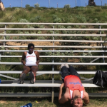 Oluyemisi sitting on bleachers with a friend stretching upside down below her