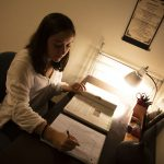 student studying at desk with lamp
