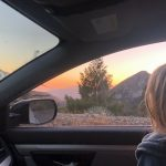 looking out car window at sunset over mountains