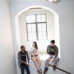 3 students on window seat in dorm stairwell