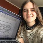 Nelia holding up her laptop