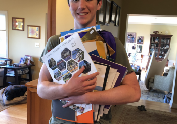 Bryce holding a bunch of college brochures
