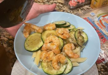 hand holding plate of garlic shrimp on zucchini
