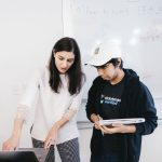 professor explaining something to student on laptop