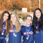 Nelia with 3 soccer teammates in uniforms