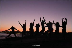 silhouettes of 8 students stretching, dancing on beach at sunset