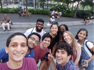 group of 9 students smiling for selfie shot outside