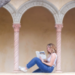 Lily sitting on ledge between columns, reading a book