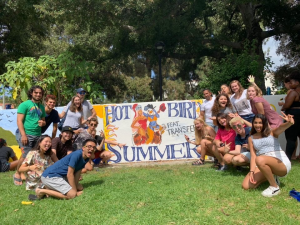 Pomona students with banner welcoming transfer students