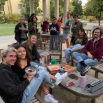 group of students sitting in chairs outside eating pizza