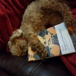 Leslie's small dog cuddling a copy of Hesiod