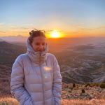 Dede in puffer jacket with setting sun and foothills behind her