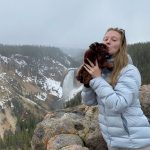 Dede in puffer jacket, kissing a stuffed bison, with snowy mountains in background