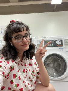 Leslie giving peace sign in front of washing machine