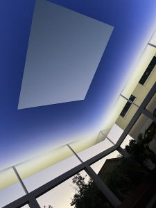 view upward of art installation, Sky Space, with blue light surrounding gray rectangle