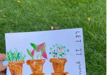 grass in background with hand holding card with painting of flower pots
